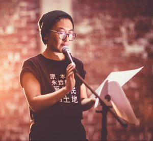 Jinghua Qian reading at a microphone