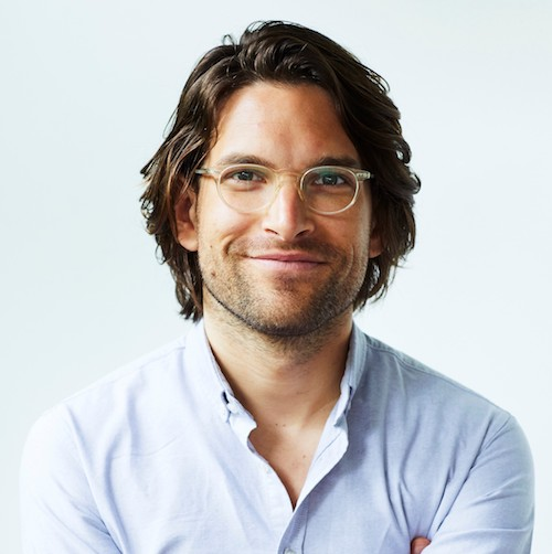 A white man with shoulder-length brown hair and glasses in a white shirt